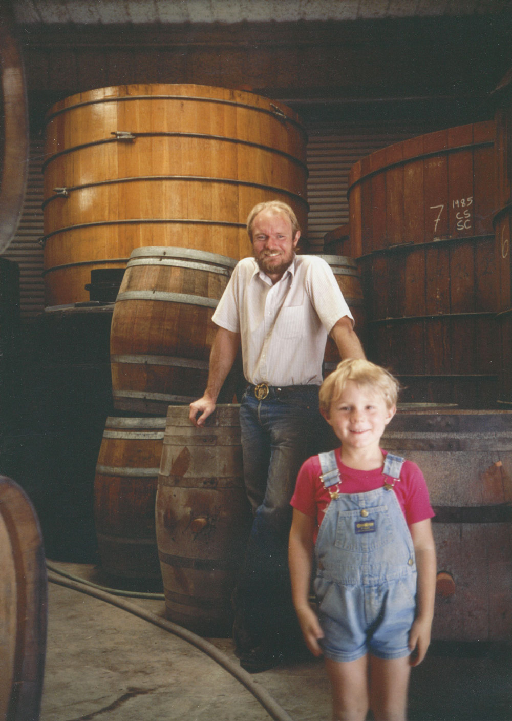 Joel Peterson and 7-year-old Morgan Twain-Peterson in Ravenswood Winery, in the 1980s