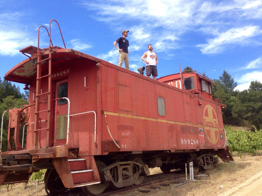 Luke and Cody standing atop the famous red caboose at the top of Nervo Ranch